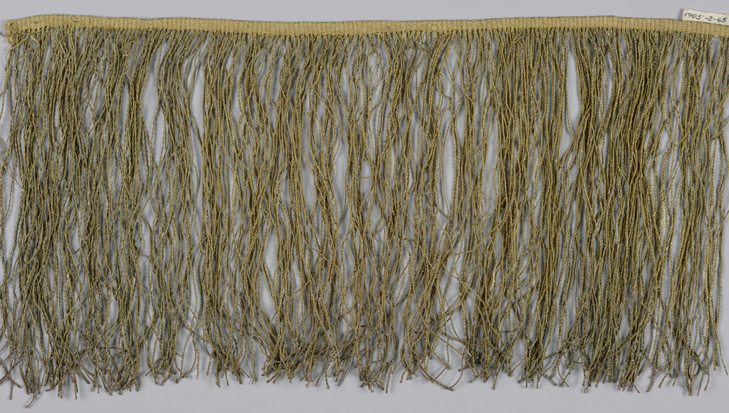 Gold fringe with a plain-woven heading and a fringe skirt of twisted loops.