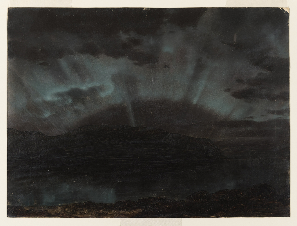"""The """"Northern Lights"""" hang in a green blanket over a promontory of Mount Desert Island, and are reflected in still water in the foreground. Night scene."""