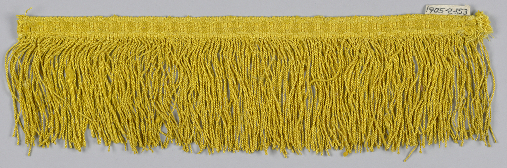 Yellow fringe with woven heading in a chain design. Skirt threads are looped and twisted.