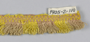 Pink and yellow fringe with a plain-woven heading. Skirt threads are arranged to form stripes.