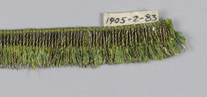 Heading of green silk with an overlay of gold threads. Gold and silk threads form a very narrow looped fringe on one border.