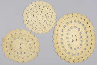 Two oval and one round mat made by stitching together white cotton fabric braid which has been flat braided and coiled.