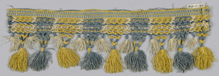Blue, yellow and white fringe with a checkerboard heading and stripes. Trellis band pattern on top of skirt threads arranged in stripes and tied into tassels of two lengths.