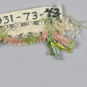 Dress trimming of white silk band with scallops of pink and green chenille and ornaments of colored floss silk threads with knots.