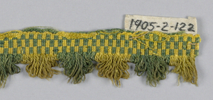 Fringe with a green and yellow checkerboard heading. Skirt threads are looped, arranged in scallops, and are alternately green and yellow.
