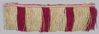 Red, off-white and tan fringe with a patterned heading. Skirt of red and off-white threads is looped, twisted and arranged to form colored stripes.