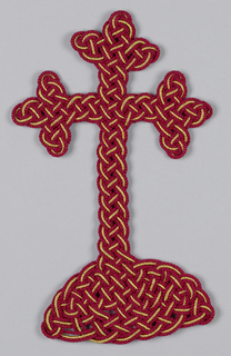 Cross on a mound in red and gold knitted plaits.