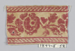 Fragment has a design of red roses with buds and leaves set between upper and lower borders of diagonal lines on a tan ground.