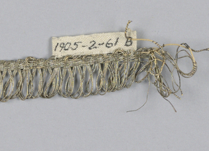 Silver fringe with a plain-woven heading and a skirt of loops.
