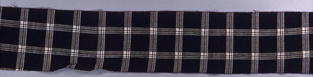 Narrow fragment of black and white plaid.