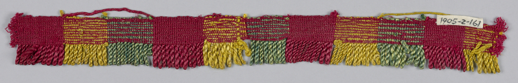 Red, yellow and green fringe with a soumak heading. Skirt threads are looped and twisted to form stripes.