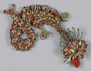 Knotted design of dragon-like creature with claws in red and gold.