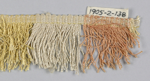 Fringe in pink, tan, yellow, and white with a plain-woven heading. Skirt threads are arranged to form pink, tan, yellow and white stripes.