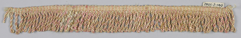 Fringe in pink, yellow and gold with a plain-woven heading. Skirts threads are made up of pink, yellow and gold threads that are twisted and looped.