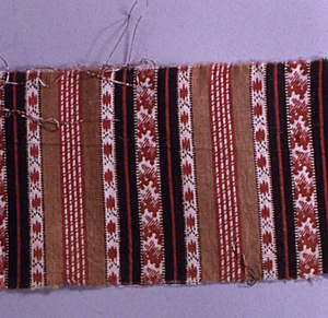 Fragment printed in red, brown and black on a white ground in a design of solid vertical stripes alternating with stripes of geometric patterning.