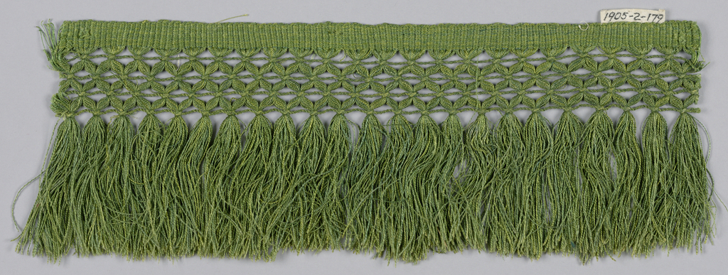 Green fringe with a plain weave heading, band in a trellis pattern and skirt threads.
