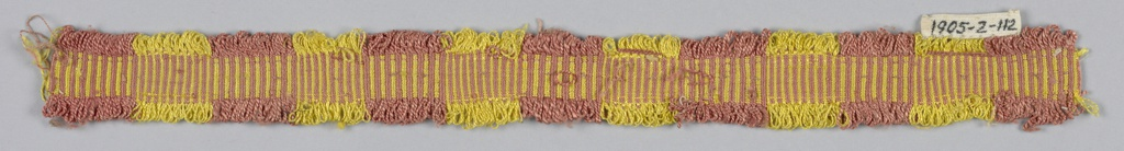 Heading woven in a pattern of alternating pink and yellow stripes. Weft threads arranged to form narrow looped fringe on either side.