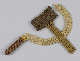 Knitted hammer and sickle symbol in browns and beige.