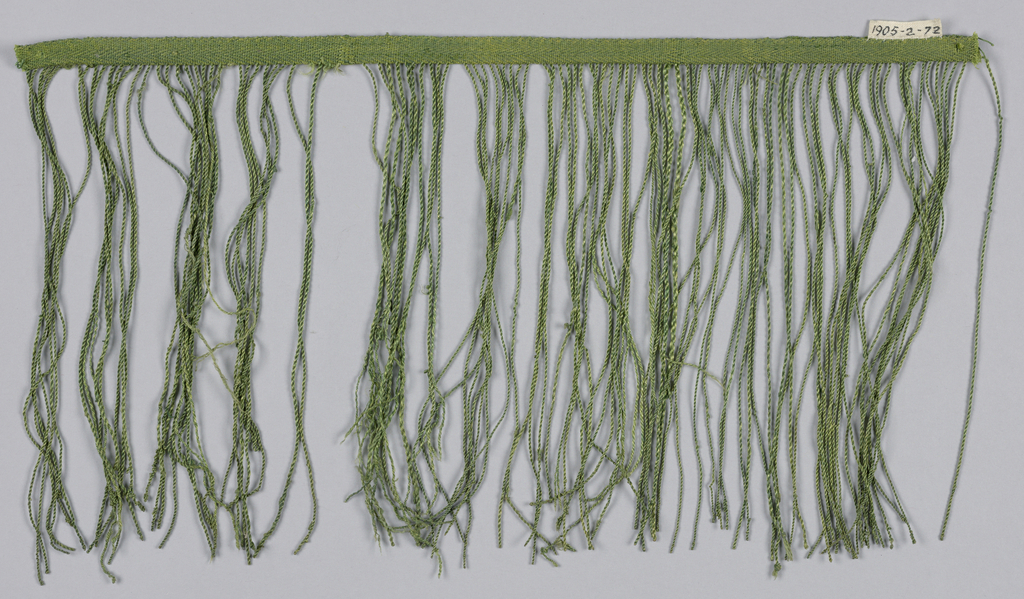 Green fringe is formed by allowing areas of weft to hang from the center of the band which is woven in a chevron pattern.