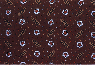 Dark reddish brown ground with an allover design of flowers, Greek frets and small dots in red, white, light brown and black.