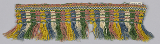 Green, pink, yellow, blue and white fringe with a checkboard heading, trellis band pattern and skirt threads arranged in stripes.