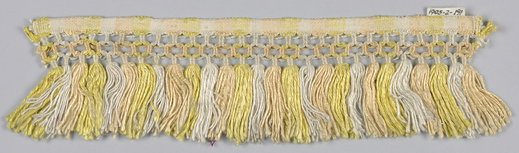 Yellow, orange and white fringe with a plain weave heading. Trellis band and skirt threads arranged to form stripes.
