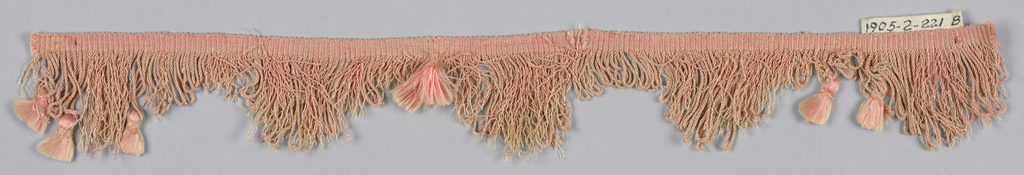 Pink fringe with a heading and a looped skirt with pointed edges ornamented with tufts of floss.