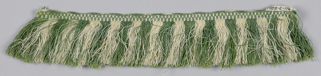 Green and white fringe with a heading in a checkerboard pattern. Skirt threads are arranged to form stripes.