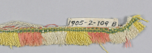 Fringe with a green striped woven heading. Pink, white, yellow and green skirt threads are arranged to form colored stripes.