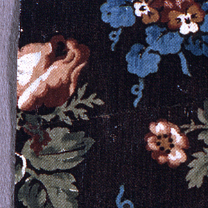 Piece of printed, glazed chintz with blue and brown flowers and green leaves on dark brown ground.