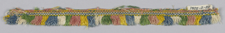 Pink, yellow, blue, white and green fringe with a woven heading. Skirt threads arranged to form colored stripes.