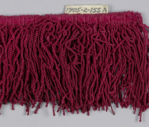 Red fringe with an ornamental heading and a skirt of looped and twisted threads.