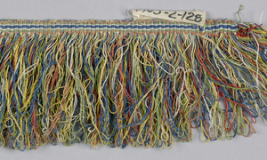 Fringe in green, yellow, red, blue, and white striped heading. Skirt threads are looped for a polychrome effect.