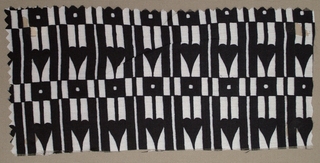 Black and white geometric pattern. In the narrower bands, black squares with white centers alternate with white squares with black lines through the center. In the wider bands, a black spade-like figure in a white rectangle alternates with narrow black rectangles with white lines through the center.