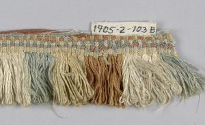 Brown, white, blue and off-white fringe with a plain-woven heading and a skirt of looped threads arranged to form colored stripes.
