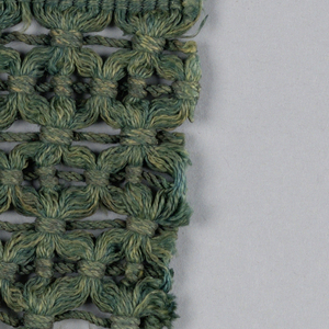 Green fringe with a plain weave heading and skirt threads tied at the top by a running thread inserted into the trellis band.