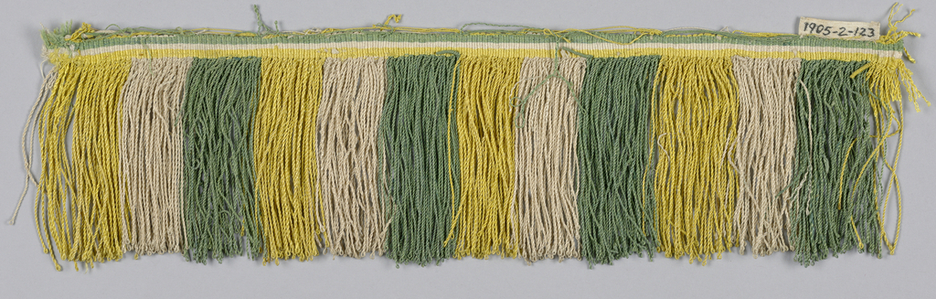 Fringe with a yellow, green and white striped heading. Skirt threads, looped and twisted, are in yellow, green, and white stripes.