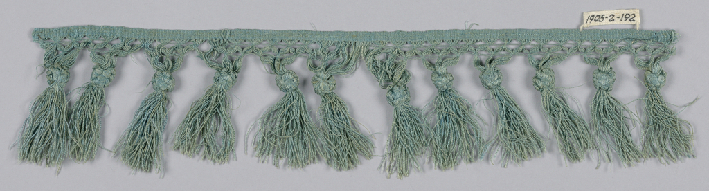 Blue fringe with a trellis band and tied skirt threads that form tassels.