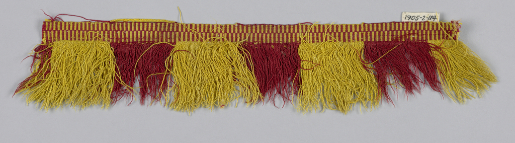 Red and yellow fringe with a heading in a checkerboard pattern. Skirt threads are arranged in stripes.