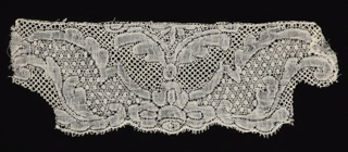 "Fragment of Binche-style lace with symmetrical design of paired scrolling leaves. ""Cinq trous"" and ""snowball"" ground. Scalloped edge."