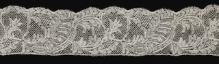 Binche-style border showing floral sprays and ribbons in a serpentine pattern.
