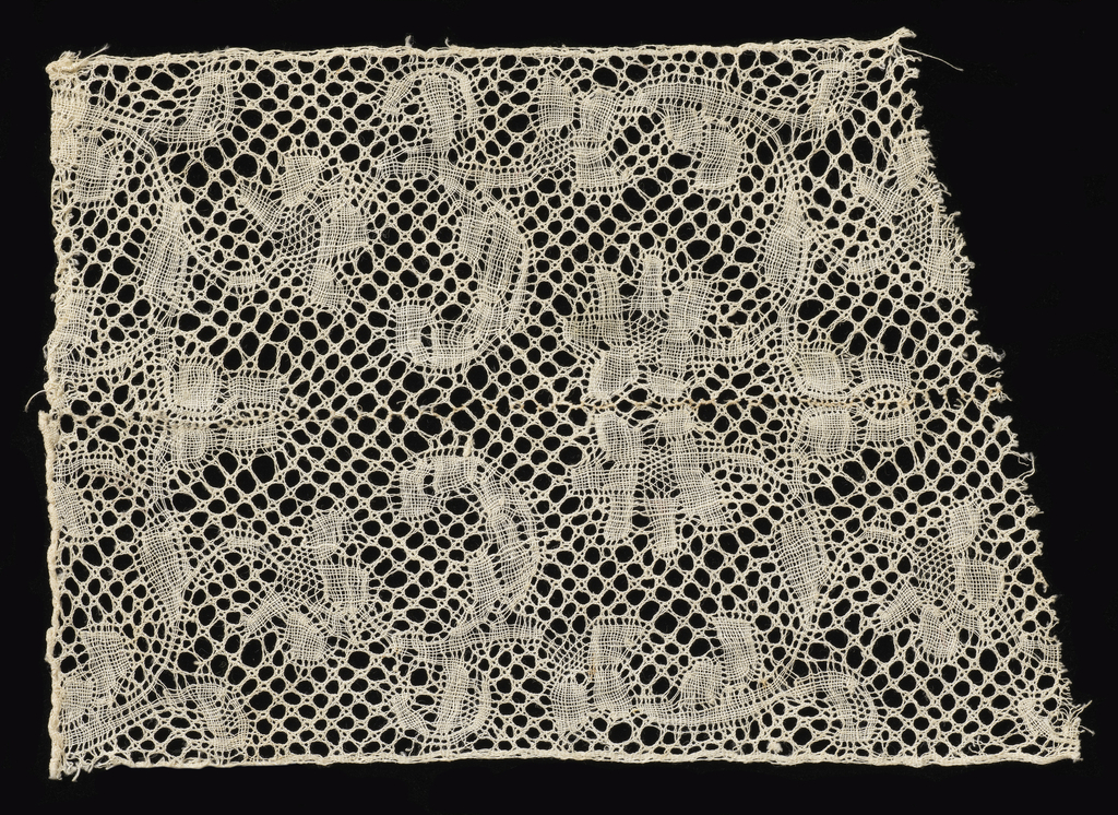 Binche-style fragment with a border design of flowering branches curving up and back from the edge of the piece. Cinq trous ground. Design repeated in reverse direction in the upper half of the piece. Fragment is two pieces stitched together in the middle.