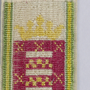 A shield under a crown showing bands of checkerboard (red and yellow) within a red band with yellow crosses.  White ground with green and yellow border stripes.
