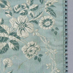 Light blue silk ribbon brocaded in a blue and white floral pattern comprised of a curvilinear floral vine that intersects with a slender vine of small leaves.