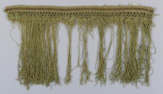 Green and metallic gold fringe with a soumak heading. Trellis design in metallic thread above a skirt of green threads.