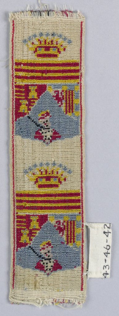 Head and shoulders of soldier with gun shown against arms under crown; in red, yellow, and blue on white.