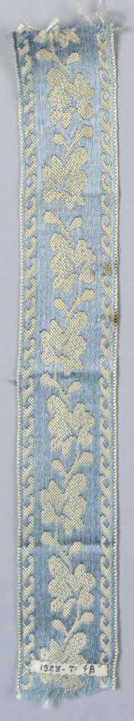 Blue satin ground with ivory leaves turning alternately left and right; wave design in border.