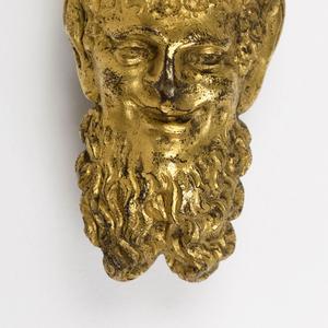 Head of a bearded satyr with long horns.