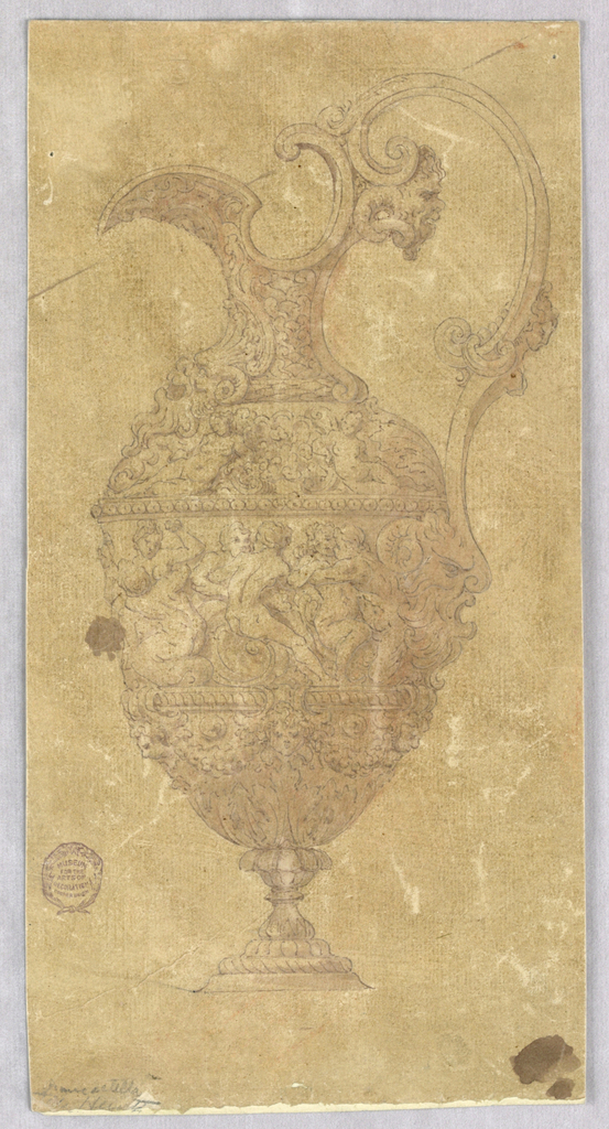 An ewer, spout facing left. The C-curve handle decorated with threemasks. Another mask as the anti-fix and more at base of vase. High relief figural decoration throughout.