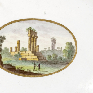 Assymetrical ovoid dish with scalloped rim, scrolled at left and right; rim decorated with wide blue band between thin gilt lines; in center, oval medallion with gilt border, showing landscape with two figures among classical ruins.